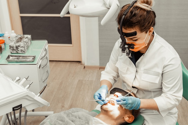 Tandarts jonge vrouw behandelt een patiënt een man. de arts gebruikt wegwerphandschoenen, een masker en een hoed. de tandarts werkt in de mond van de patiënt, gebruikt een professioneel hulpmiddel.