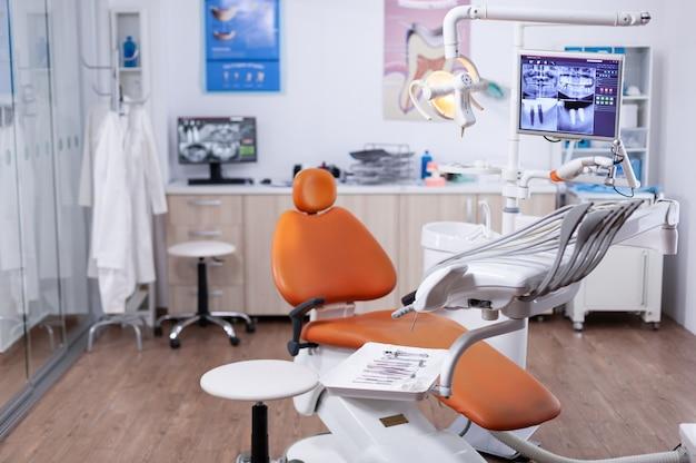 Tandarts kantoor interieur met moderne stoel en speciale dentisd apparatuur. het interieur van de stomatologiekliniek.