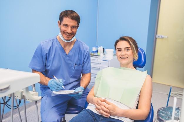 Tandarts mannelijke arts met gelukkige vrouwelijke patiënt schrijft een conclusie en diagnose in de tandartspraktijk