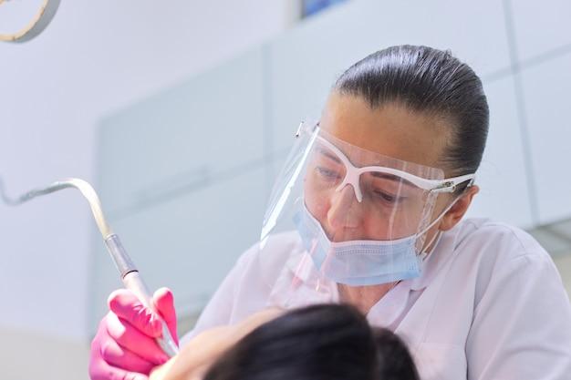 Tandarts met assistent die tanden behandelt aan een patiënt in de tandheelkundige kliniek