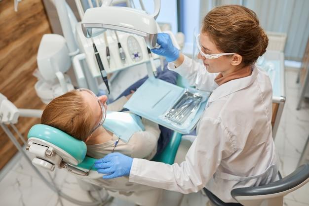 Tandarts met behulp van medische instrumenten tijdens tandheelkundige ingreep met patiënt bij kliniek