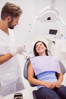 Tandarts met lachende vrouwelijke patiënt