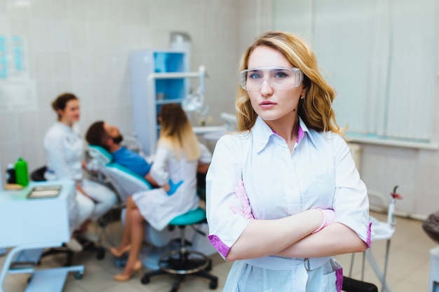 Tandarts. portret van een professionele tandarts op de achtergrond van een werkend team van artsen. concept van medisch onderwijs en medische verzekering.