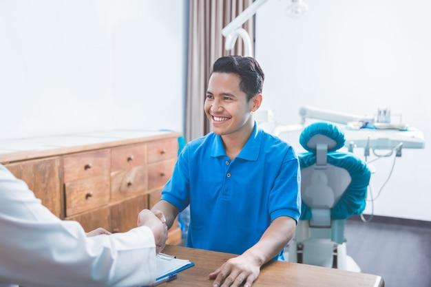 Tandarts praten met zijn patiënt bij tandheelkundige zorg kliniek en schudden