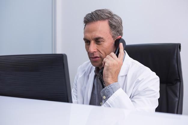 Tandarts praten over de telefoon zittend door de computer