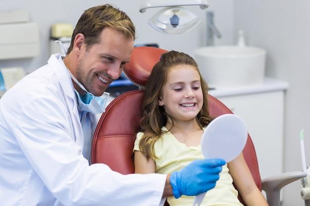 Tandarts spiegel tonen aan jonge patiënt in tandheelkundige kliniek