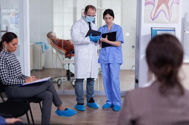 Tandarts toont tanden x-ray herziening met verpleegster arts en assistent werken in moderne drukke stomatologische kliniek, patiënten zittend op stoelen bij de receptie het invullen van tandheelkundige formulieren wachten.