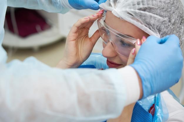 Tandarts zet beschermende bril op patiënt vrouw voordat tanden genezen in het kantoor van de tandarts