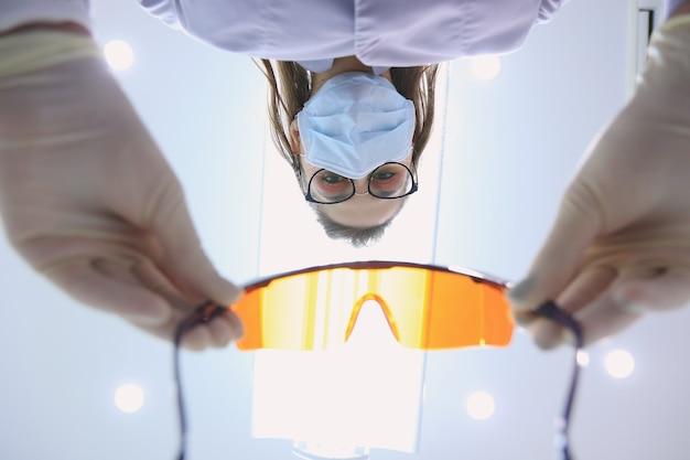 Tandarts zet bril op de patiënt, onderaanzicht door de ogen van de patiënt