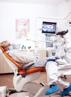 Tandartsassistent die een hazmat-pak draagt tegen het coronavirus en aantekeningen maakt in een gesprek met een oudere patiënt. oudere vrouw in beschermend uniform tijdens medisch onderzoek in tandheelkundige kliniek.