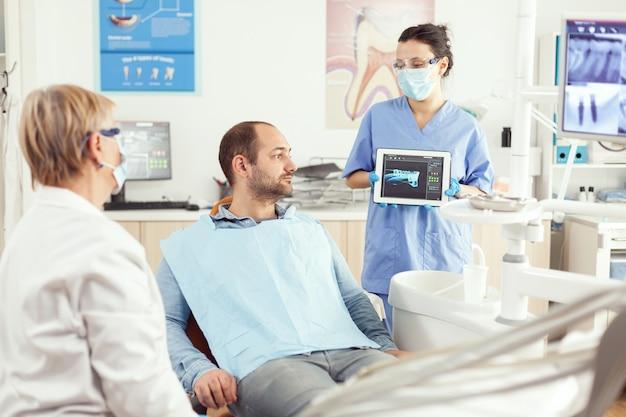 Tandartsassistent die tandenradiografie op het computerscherm van tablet-pc toont aan een zieke patiënt op het kantoor van de tandheelkundige kliniek