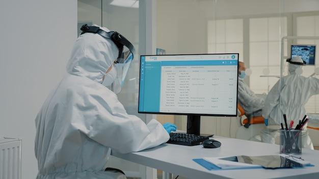 Tandartsassistente die aan de computer werkt bij de tandheelkundekliniek