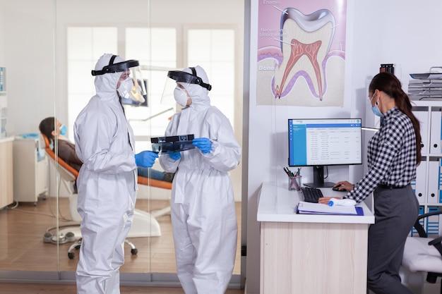 Tandartsassistente in gesprek met arts patiënt diagnose houden van sociale afstand, gekleed in pbm-pak, gezicht afgeschermd, tijdens wereldwijde pandemie met coronavirus met röntgenfoto