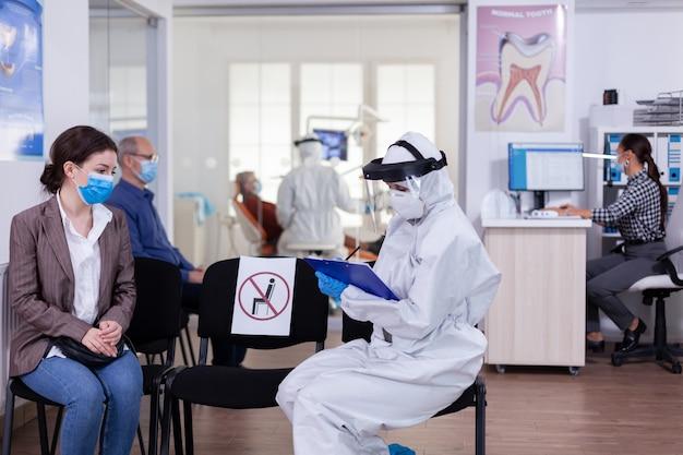 Tandartsassistente met pbm-apparatuur in gesprek met patiënt vóór consultatie tijdens coronavirusepidemie zittend op stoelen in wachtruimte op afstand houden