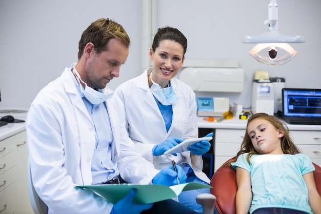 Tandartsen die de rapporten controleren terwijl de patiënt op tandartsstoel ligt