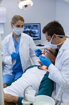 Tandartsen die een mannelijke patiënt met hulpmiddelen onderzoeken