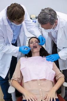 Tandartsen die een vrouwelijke patiënt met hulpmiddelen onderzoeken