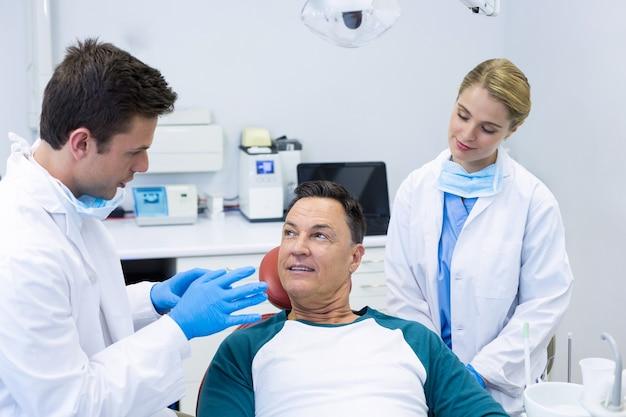Tandartsen die interactie hebben met een mannelijke patiënt