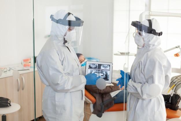 Tandartsen gebruiken in het algemeen tablet met uitleg over tandheelkundige röntgenfoto's in stomatologisch kantoor tijdens corona...