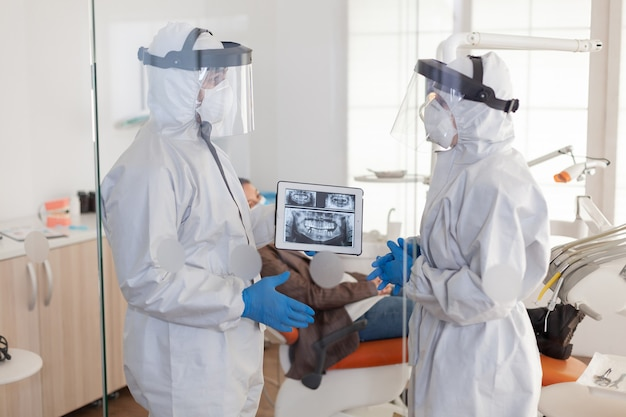 Tandartsen gebruiken in het algemeen tablet met uitleg over tandheelkundige röntgenfoto's in stomatologisch kantoor tijdens coronavirus