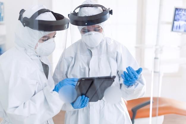 Tandartsen in tandartspraktijk gekleed in ppe-pak en gezichtsmasker met tablet-pc. stomatologieteam in tandartspraktijk met beschermend pak tegen besmettelijk coronavirus tijdens wereldwijde pandemie.