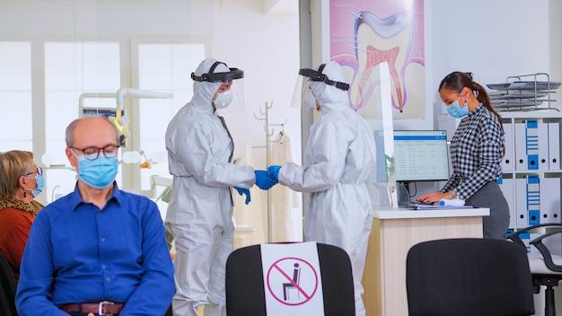 Tandartsen met een beschermingspak die de röntgenfoto van de tanden bij de receptie analyseren terwijl de patiënt op de stoel wacht, met respect voor de sociale afstand. concept van nieuw normaal tandartsbezoek bij uitbraak van coronavirus.