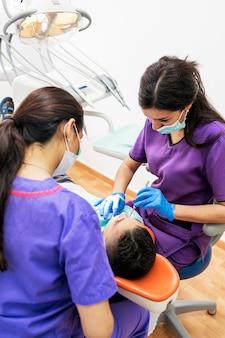 Tandartsen tijdens een tandheelkundige ingreep met een patiënt. tandartsconcept