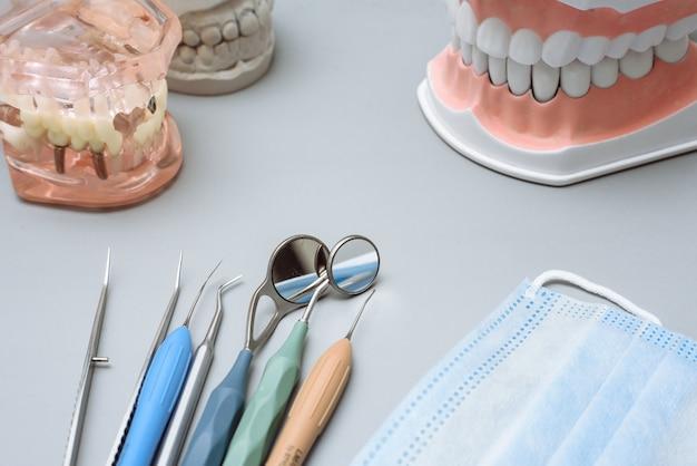 Tandartshulpmiddelen, medisch masker en kunstmatige kaken op een grijze achtergrond