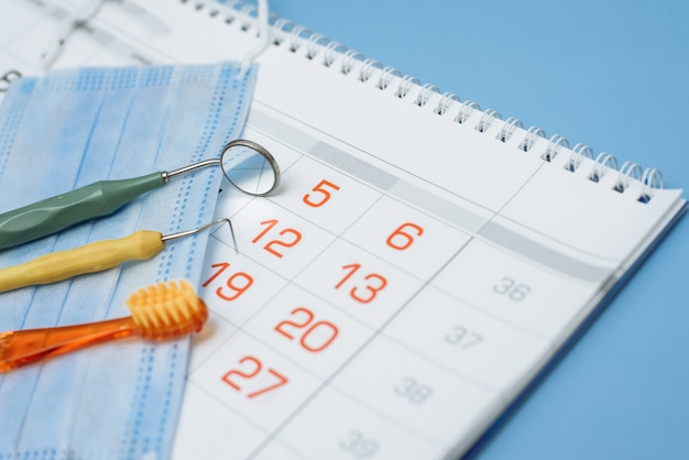 Tandartshulpmiddelen, tandenborstel, medisch masker en kalender op blauwe achtergrond