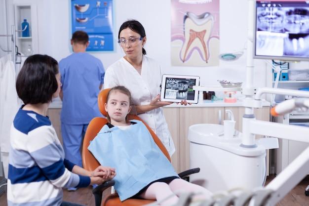Tandartsspecialist die over kaak digitale radiografie van kleine meisjespatiënt bespreekt. stomatoloog die de diagnose van tanden uitlegt aan moeder van kind in gezondheidskliniek met röntgenfoto.