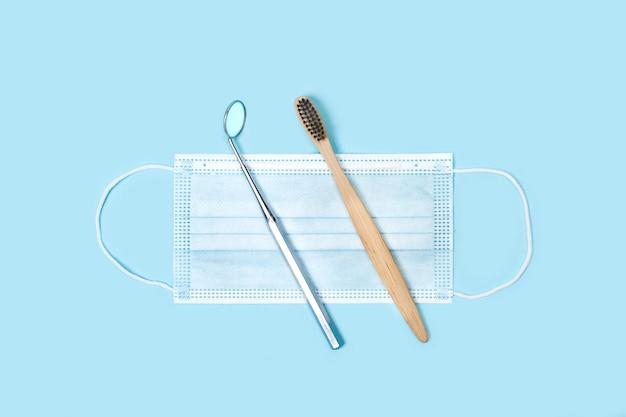 Tandartsspiegel en tandenborstel op een chirurgisch masker op een lichtblauw oppervlak