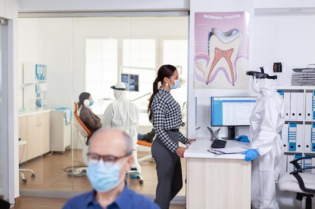 Tandartsverpleegster gekleed in pbm-pak met gezicht dat met de patiënt in gesprek is