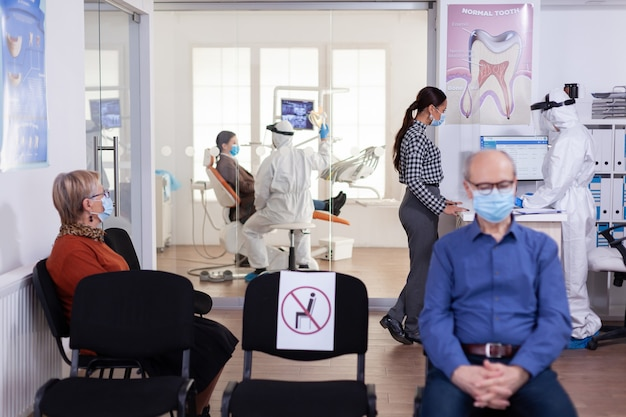 Tandartsverpleegster gekleed in pbm-pak met gezicht shyled besprekend met patiënt in stomatologiewachtkamer