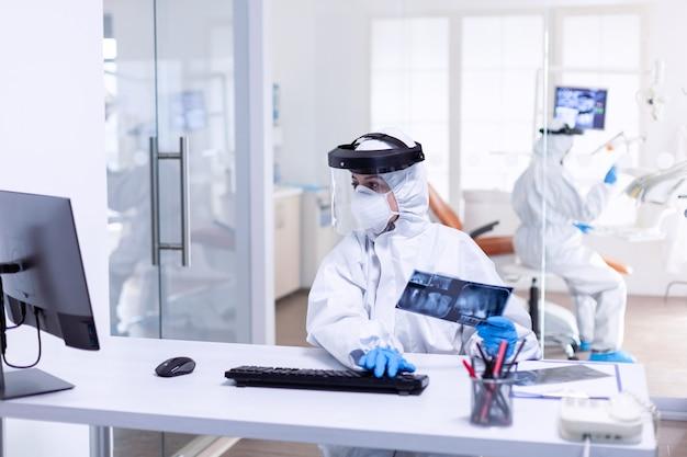 Tandartsverpleegster gekleed in ppe-pak met röntgenfoto's van patiëntentanden tijdens covid-19. medicijnteam dat als veiligheidsmaatregel beschermingsuitrusting draagt tegen een pandemie van het coronavirus bij de tandheelkundige receptie.