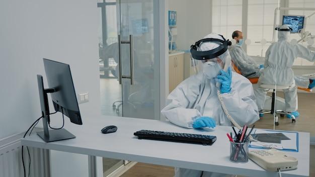 Tandartsverpleegster in beschermingspak zittend aan bureau