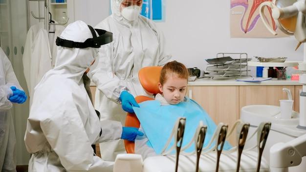 Tandartsverpleegster in overall die een tandslab aan de patiënt van een kind geeft vóór stomatologisch onderzoek tijdens de covid-19-pandemie. assistent en pediatrische arts met beschermingspak, gelaatsschermmaskerhandschoenen