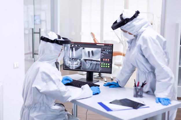 Tandartsverpleegster in pak tegen covid-19 die tandenröntgenfoto toont aan stomatolog. medisch specialist die beschermende kleding draagt tegen coronavirus tijdens wereldwijde uitbraak, kijkend naar radiografie in tandartspraktijk.