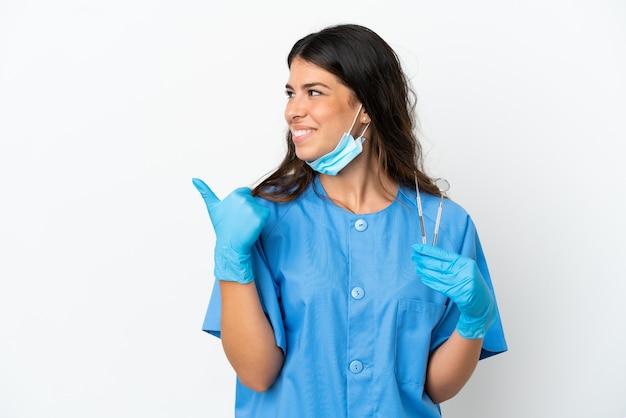 Tandartsvrouw die gereedschap over een geïsoleerde witte achtergrond vasthoudt en naar de zijkant wijst om een product te presenteren