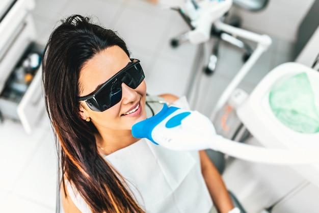 Tanden bleken in de tandheelkundige kliniek voor mooie vrouwelijke patiënt