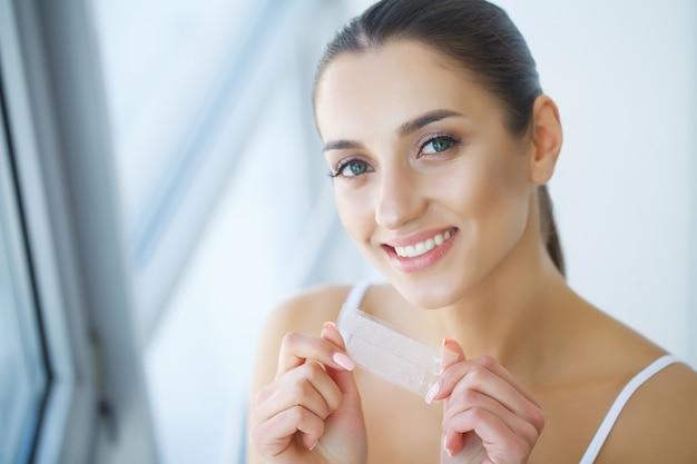 Tanden bleken. mooie lachende vrouw met whitening strip. beeld