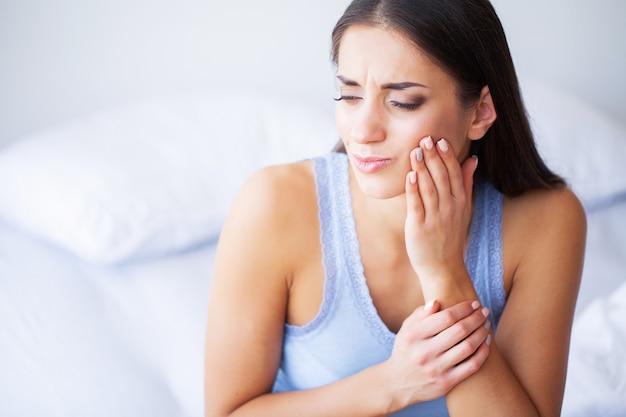 Tanden probleem. vrouw gevoel tandpijn. close-up van een mooi droevig meisje dat aan sterke tandpijn lijdt. aantrekkelijke vrouw gevoel pijnlijke kiespijn. tandgezondheid en zorgconcept