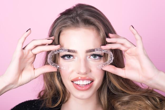 Tanden zorg. orthodontische apparaten. gevoelige jonge vrouw houdt transparant orthodontisch apparaat vast. tandenhouder. close up van plastic transparante houder in de hand van gevoelige vrouw.