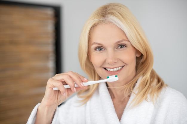 Tanden zorgen. glimlachende blonde vrouw haar tanden poetsen en op zoek gelukkig