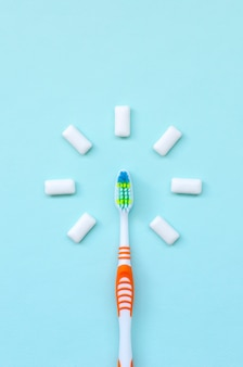Tandenborstel en kauwgom liggen op een pastelblauwe achtergrond