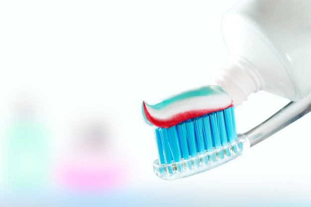 Tandenborstel en tandpasta op onscherpe achtergrond