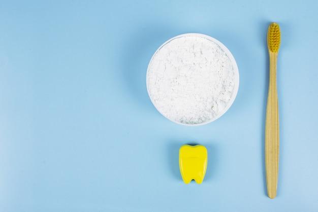Tandenborstel en tandzijde en tandpoeder op een blauwe achtergrond. mondverzorging concept. zorgen voor de natuur, geen afval. copyspace