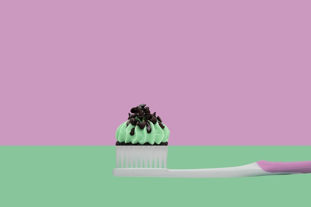 Tandenborstel met cupcakes op twee kleuren roze en groen, minimale stijl