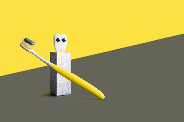 Tandenborstel met grijze tandpasta en witte stuk speelgoed tand op podium op het verlichten van gele, ultieme grijze achtergrond. concept voor tandheelkunde.