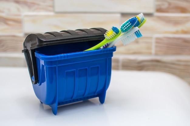 Tandenborstels in een blauwe prullenbak, veel ziektekiemen dus weggegooid