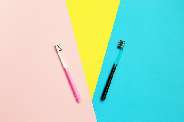 Tandenborstels op geel, blauw en roze. tanden schoonmaken. schoonheid en gezondheid. gezonde tanden.
